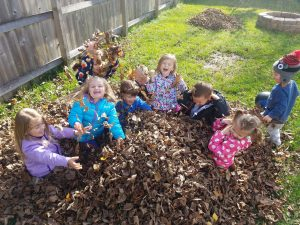 kids playing in leaves at Lauras daycare in Eagan MN