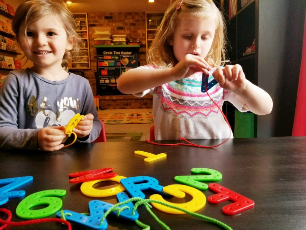 two girls practicing their letters during their preschool day